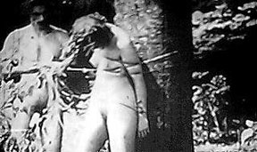 Nude woman bound to tree, nude man standing nearby, black and white